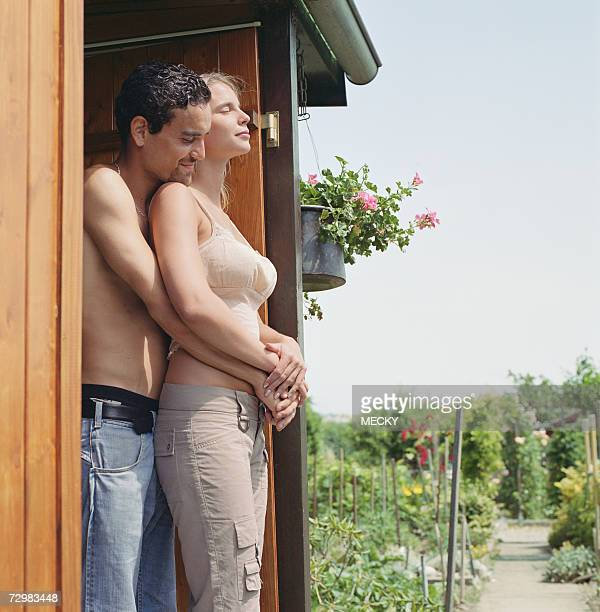 Young couple embracing in shed doorway on allotment