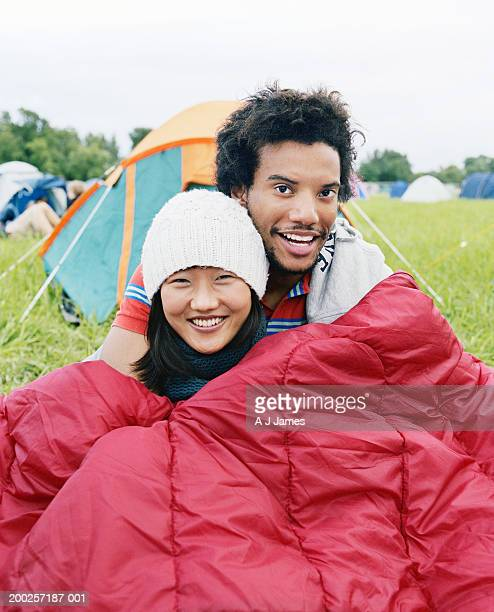 Young couple embracing in sleeping bag, smiling, portrait