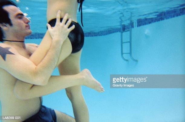 young couple embracing in swimming pool, underwater view - young men in speedos stock pictures, royalty-free photos & images