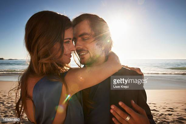 A young couple embracing on beach at sunset