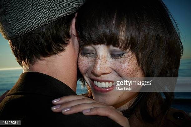 Young couple embracing on beach, smiling, close-up