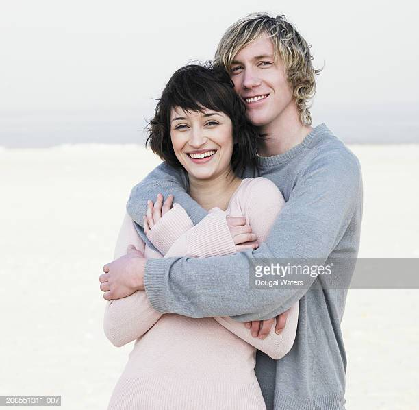Young couple embracing on beach, smiling, portrait