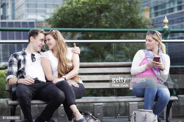 Young couple embracing on bench, single woman looking at them