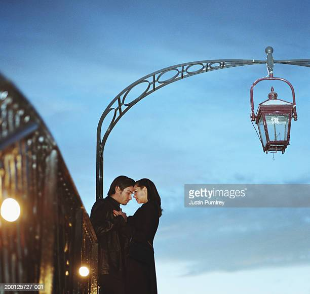 Young couple embracing on bridge, side view