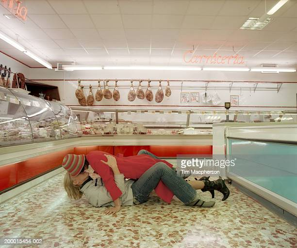 Young couple embracing on floor in meat section of  supermarket