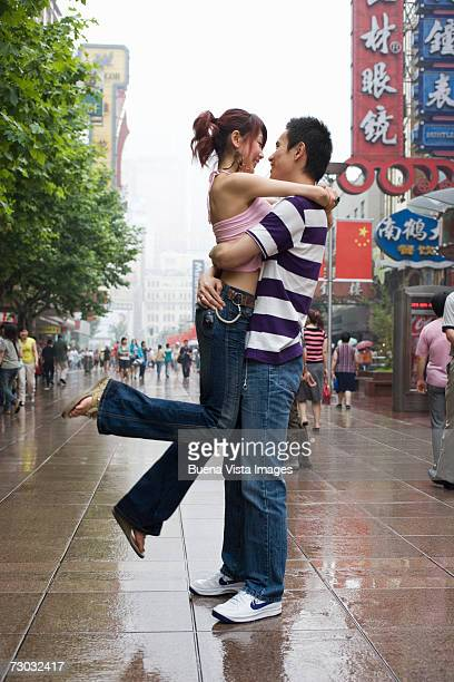young couple embracing on street, shanghai, china - wet jeans stock photos and pictures