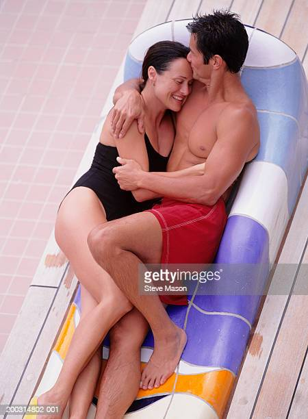 Young couple embracing on sun lounger, by pool, elevated view