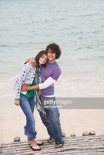 young couple embracing on  walkway by surf, portrait, elevated view - heteroseksueel koppel stockfoto's en -beelden