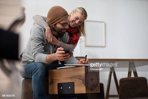 Young couple embracing one another while working in designer office