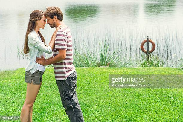young couple embracing outdoors - innocence stock pictures, royalty-free photos & images