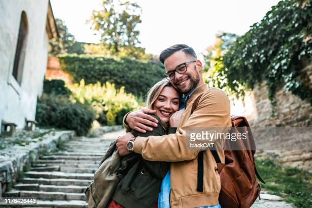 junges paar umarmt draußen - junges paar stock-fotos und bilder