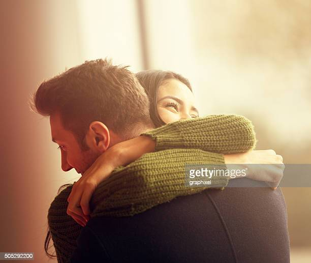 young couple embracing - aanhankelijk stockfoto's en -beelden