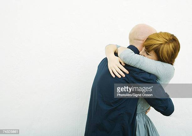 young couple embracing, side view - reconciliation stock pictures, royalty-free photos & images