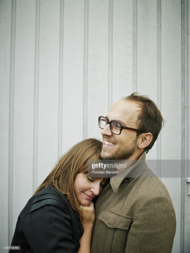 Young couple embracing smiling : Stock Photo