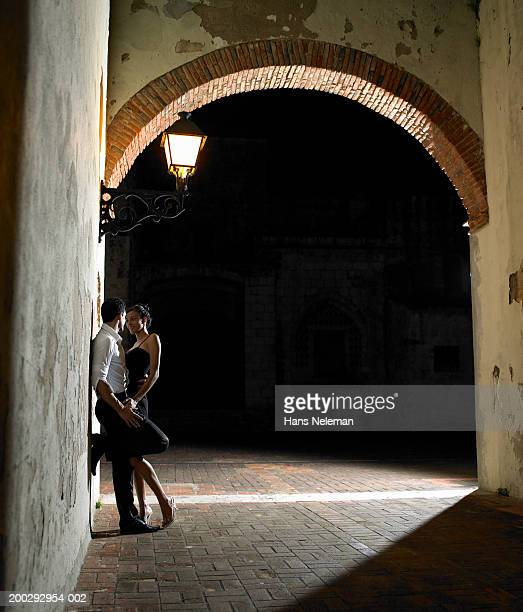 Young couple embracing under street light at night, side view