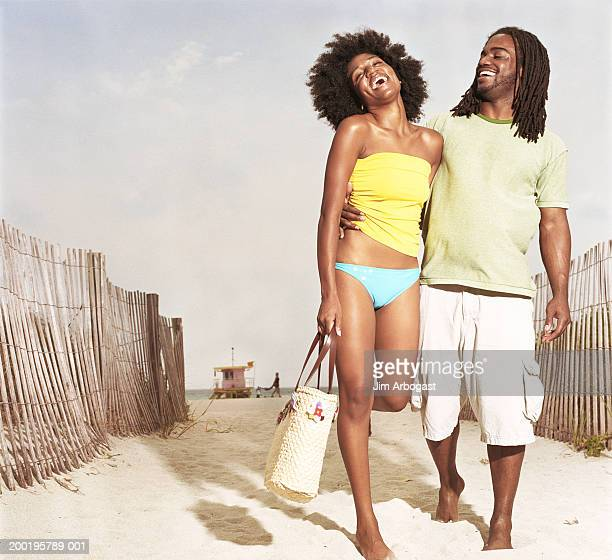 Young couple embracing, walking on beach, laughing