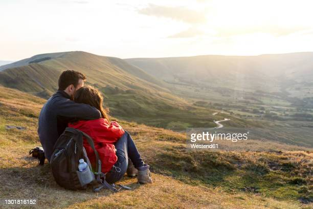 young couple embracing while looking at sunset during vacations - cliff stock pictures, royalty-free photos & images