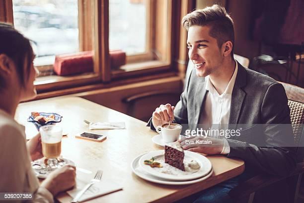 若いカップル enjoing なトークのカフェ