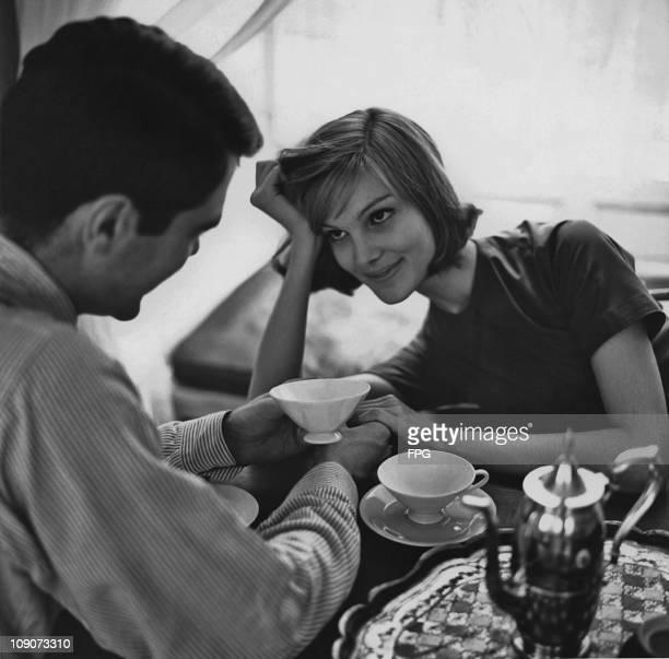 Young couple enjoy a romantic moment over coffee, circa 1965.