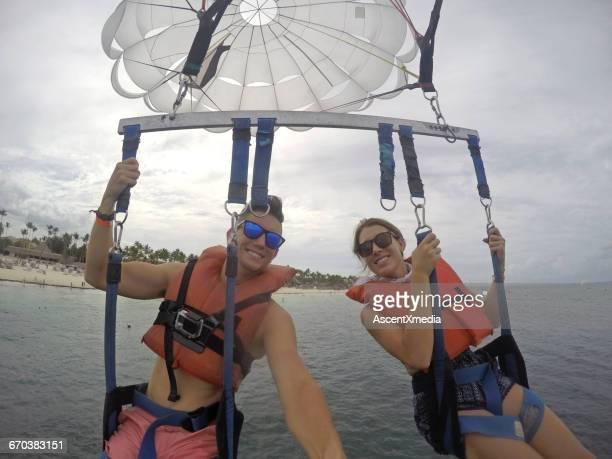 Young couple enjoy parasail ride above sea