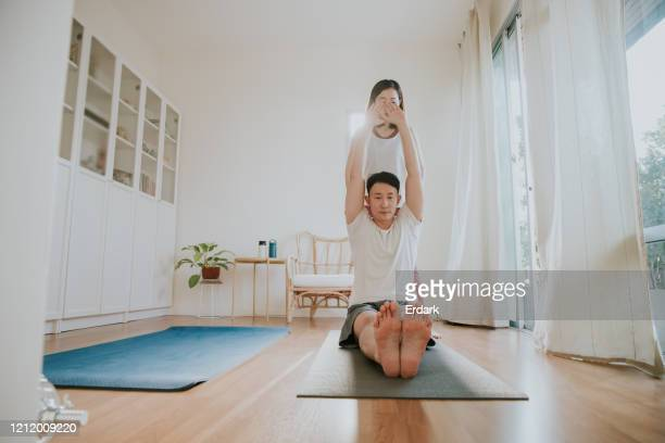 young couple enjoy playing yoga at home - herniated disc stock pictures, royalty-free photos & images