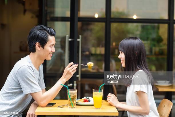 カジュアルなカフェで一緒にランチデートを楽しむ若いカップル