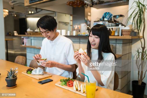 young couple enjoying a casual lunch date together at a cafe - east asia stock pictures, royalty-free photos & images