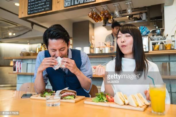 カジュアルなカフェで一緒にランチデートを楽しむ若いカップル - 昼食 ストックフォトと画像