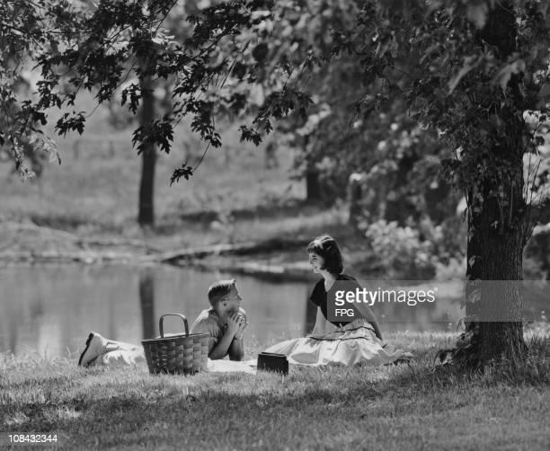 A young couple enjoying a picnic by a lake circa 1940's