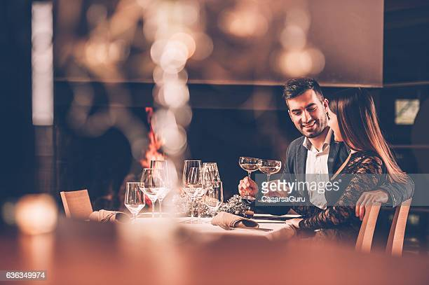 young couple enjoying a romantic dinner together - restaurante - fotografias e filmes do acervo