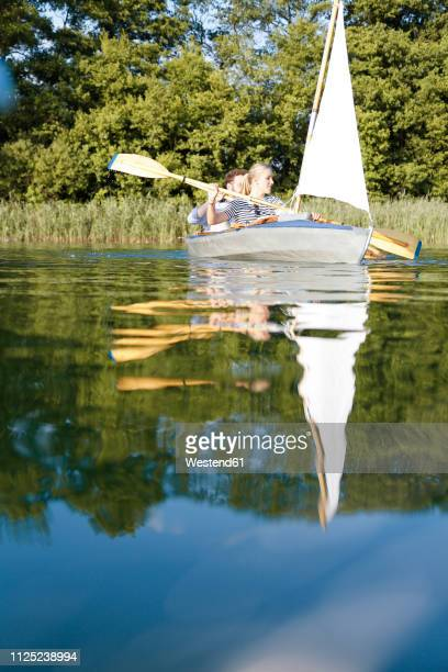 young couple enjoying a trip in a canoe with sail on a lake - 帆 ストックフォトと画像