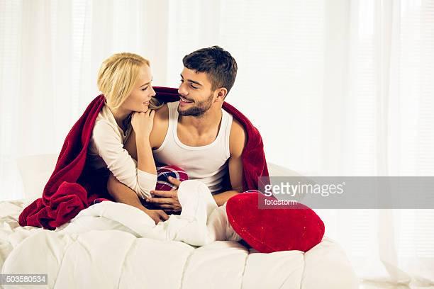 Joven pareja disfrutando de una debajo del duvet