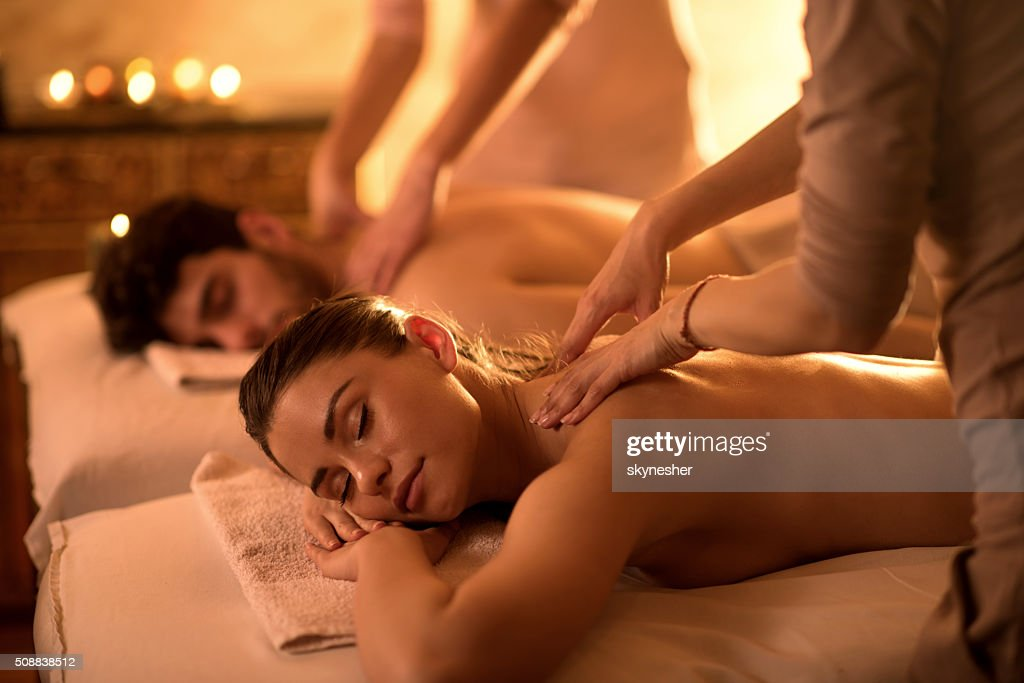 Giovane coppia che si diverte a centro benessere durante il massaggio alla schiena. : Foto stock