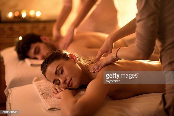 young couple enjoying at spa during back massage. - massage therapist stock pictures, royalty-free photos & images