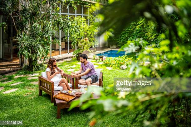 young couple enjoying breakfast in the yard - domestic garden stock pictures, royalty-free photos & images