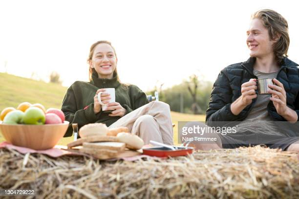 young couple enjoying coffee or hot drink while sitting on camping chair during sunrise. camping, simple, sustainable lifestyle. - simple living stock pictures, royalty-free photos & images