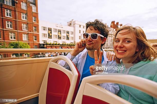 Young Couple Enjoying Double-Decker Bus ride in London