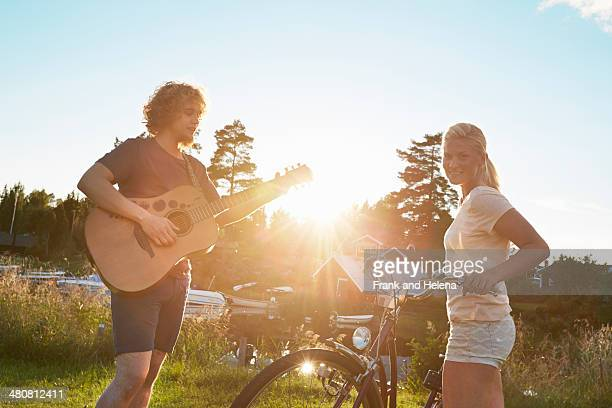 young couple enjoying guitar, gavle, sweden - blue shorts stock pictures, royalty-free photos & images