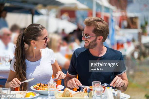 young couple enjoying healthy lunch together in greece