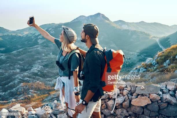 junges paar genießen wandern und dabei ein selbstporträt - hoch position stock-fotos und bilder