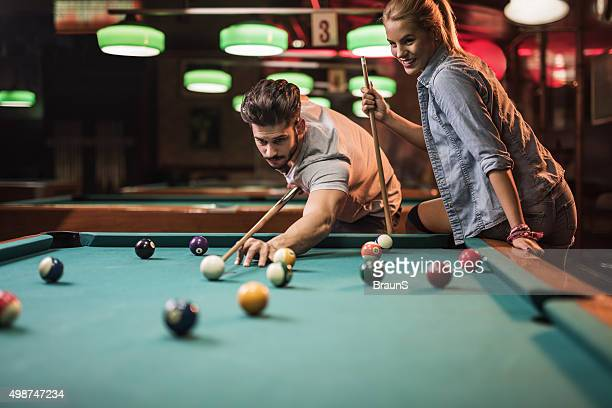 Young couple enjoying in a snooker game at pool hall.