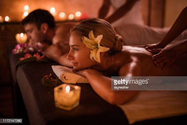 young couple enjoying in back massage at health spa. - health farm stock pictures, royalty-free photos & images