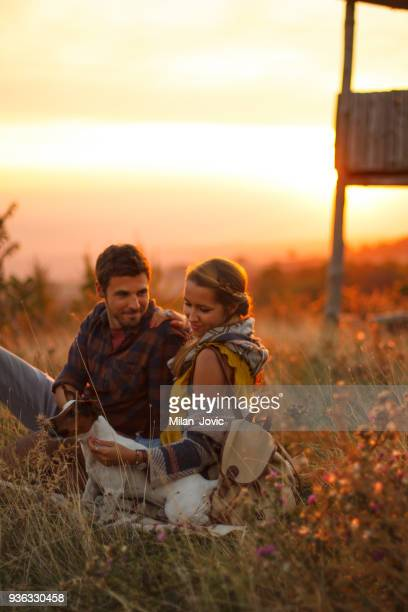 Young couple enjoying in nature with dog
