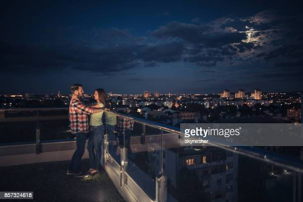 Jeune couple jouir dans une nuit romantique sur un clair de lune au balcon de l'appartement.