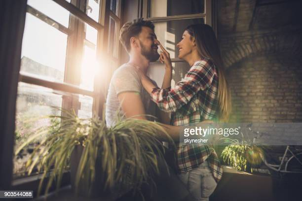 young couple enjoying in their love by the window at their new apartment. - nariz humano imagens e fotografias de stock