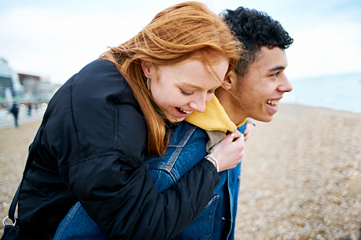 Young couple enjoying moment together at the beach in winter. Redhead teenager gets a piggyback from her boyfriend, the couple enjoying a moment together laughing and joking - gettyimageskorea
