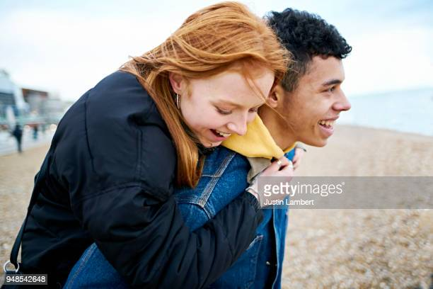 Young couple enjoying moment together at the beach in winter. Redhead teenager gets a piggyback from her boyfriend, the couple enjoying a moment together laughing and joking