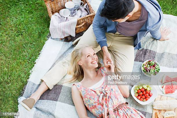young couple enjoying picnic - hamper stock pictures, royalty-free photos & images