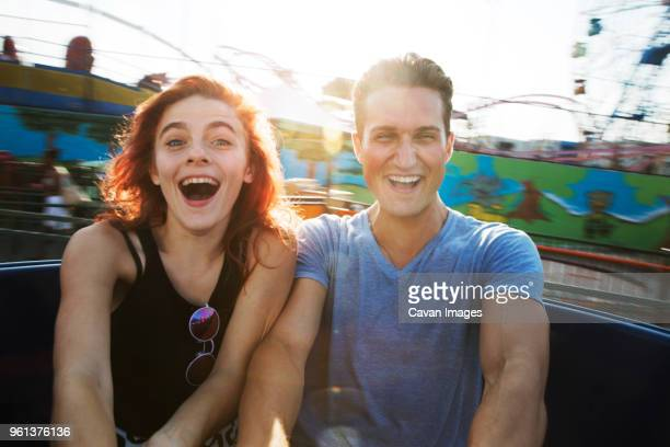 young couple enjoying ride in amusement park against sky - coney island stock pictures, royalty-free photos & images