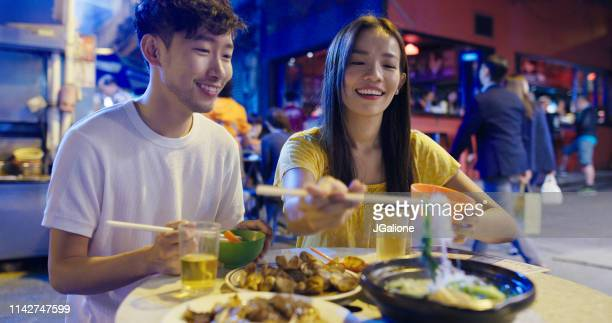young couple enjoying street food - jgalione stock pictures, royalty-free photos & images